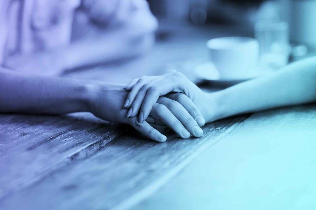 Девушка с эмпатией держит за руку парня