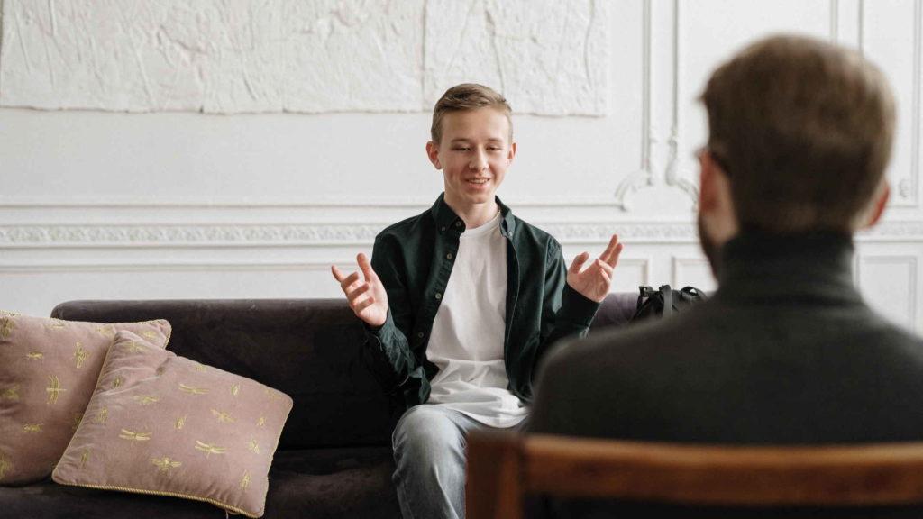 Мальчик подросток весело разговаривает с мужчиной