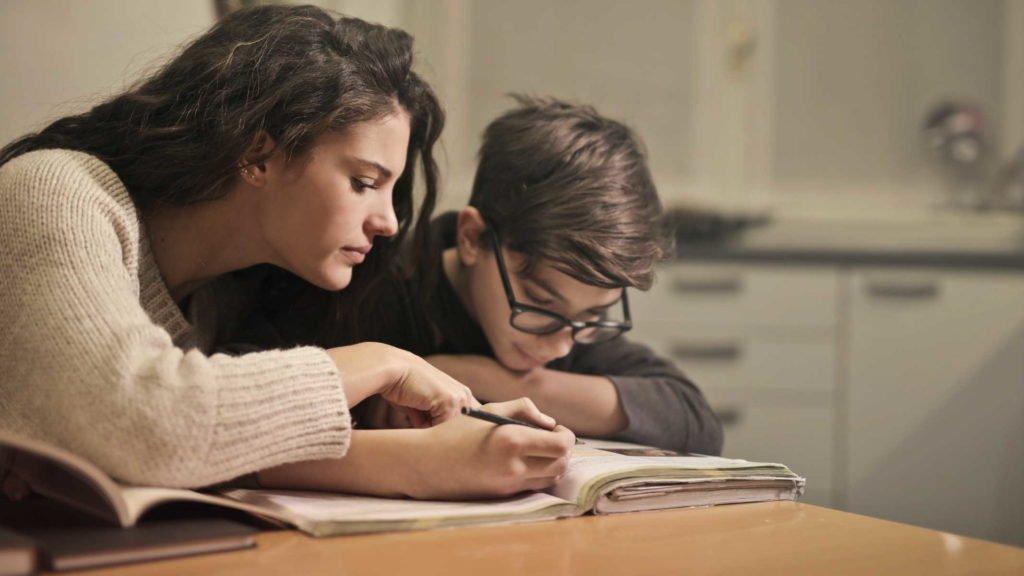 Мама помогает ребенку делять уроки