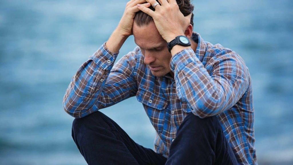 Мужчина держится за голову на фоне воде