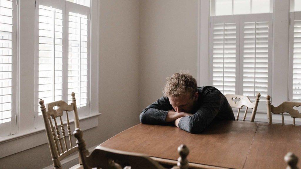 Muzhchina grustnyj lezhit na stole