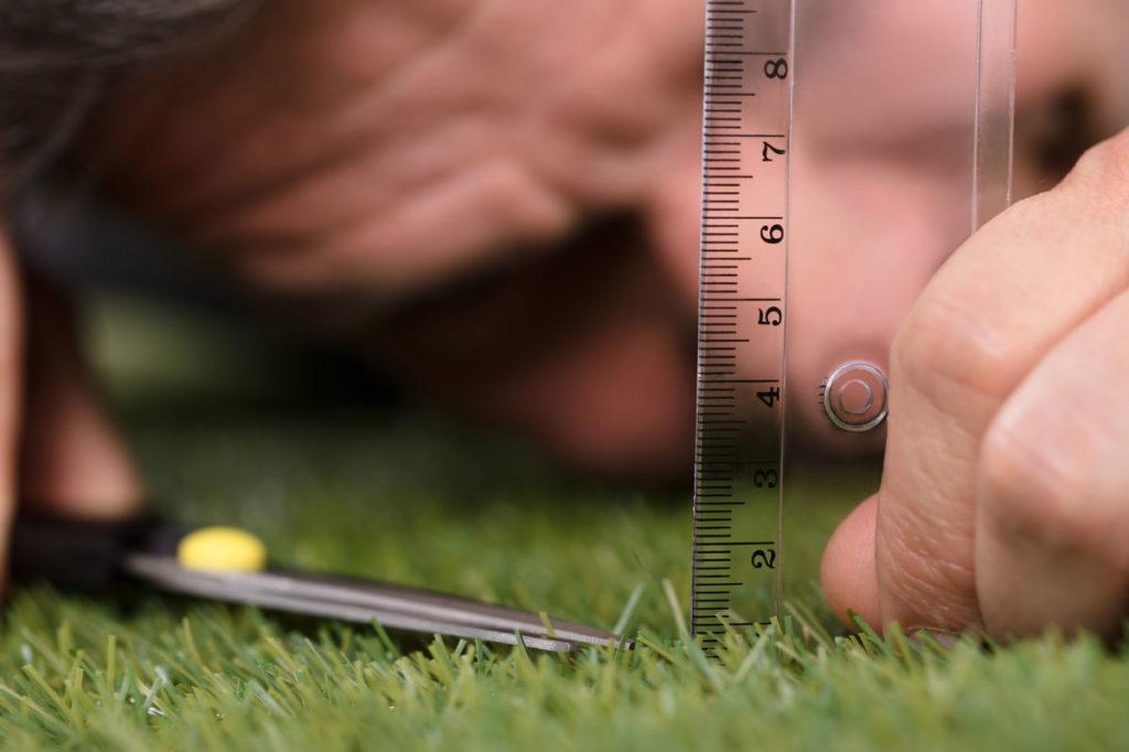 Мужчина меряет постриженную траву