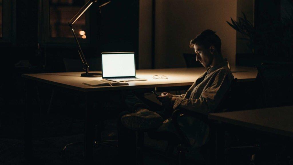 Мужчина сидит в темной комнате с включенной настольной лампой