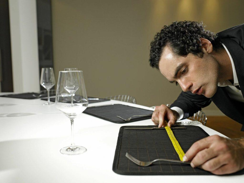 Мужчина высматривает длину коврика на столе