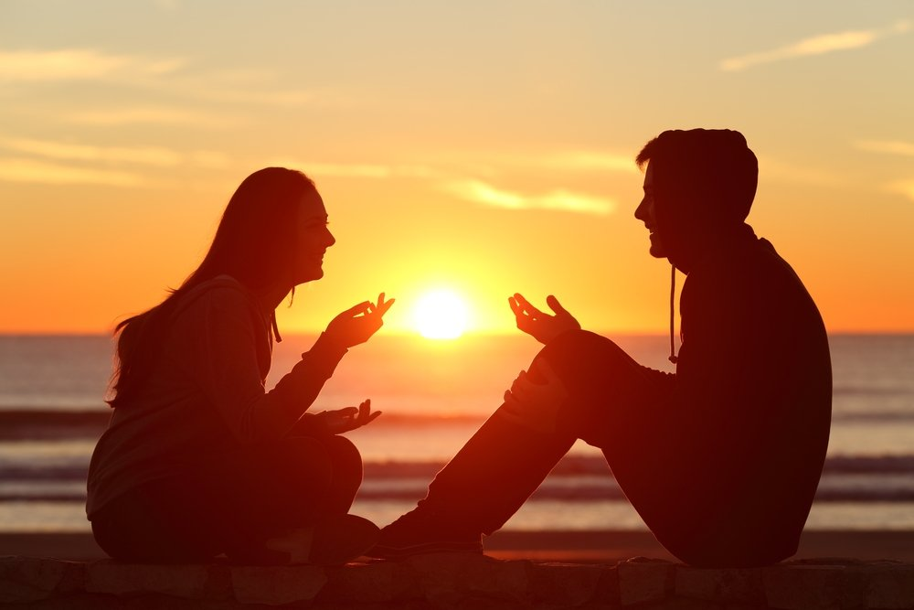 Парень с девушкой сидят при закате