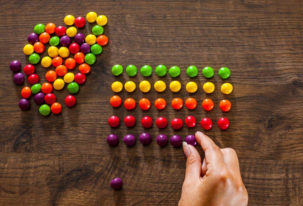 Перфекционист складывает конфетки по цветам
