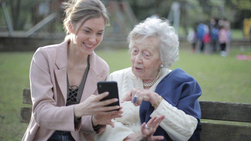 Пожилая женщина и молодая девушка сидят на лавочке в парке
