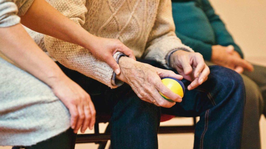 Пожилой человек держит в руках мячик