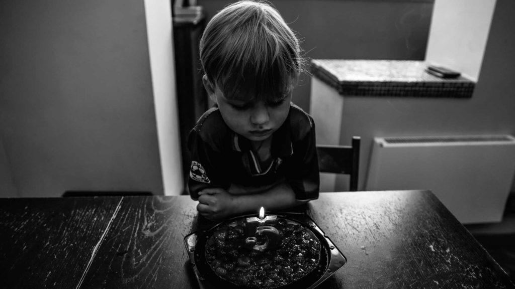 Ребенок с грустью смотрит на торт