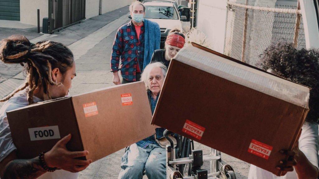 Волонтеры помогают пожилому человеку перетащить коробки