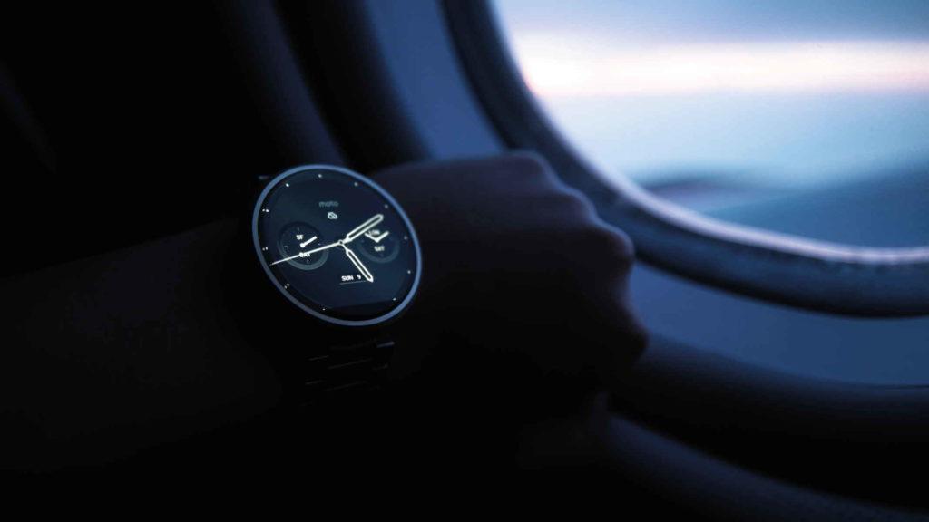 Человек в самолете смотрит время на электронных часах