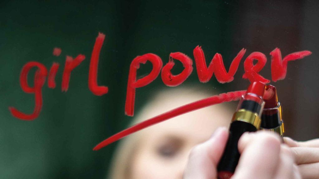 Девушка борется за феминизм с надписью женская сила