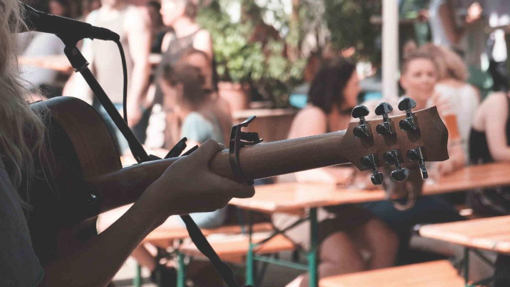 Девушка играет на гитаре в ресторане