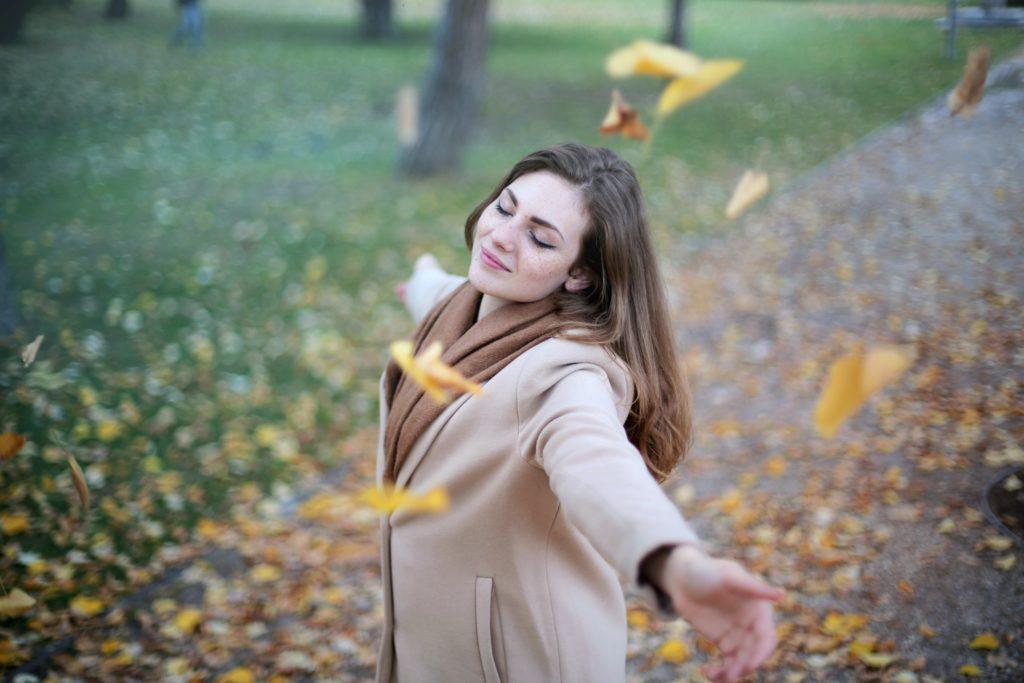 Девушка наслаждается осенним листопадом