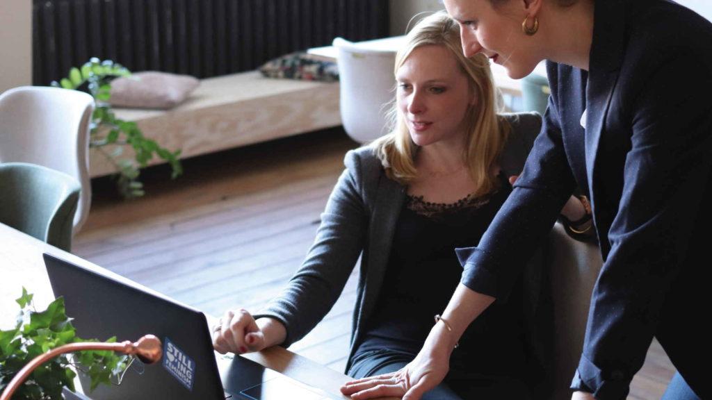 Две женщины коллеги обсуждают рабочие вопросы