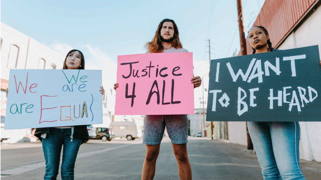 Люди стоят с плакатами в поддержку феминизма