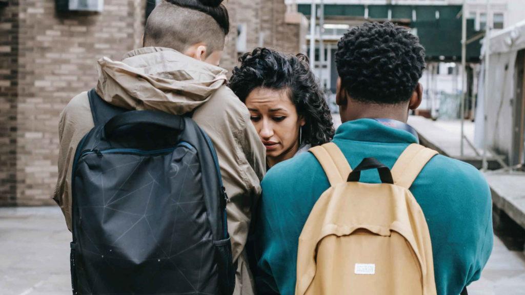 Парни после школы пытаются выясниь что то у девушки