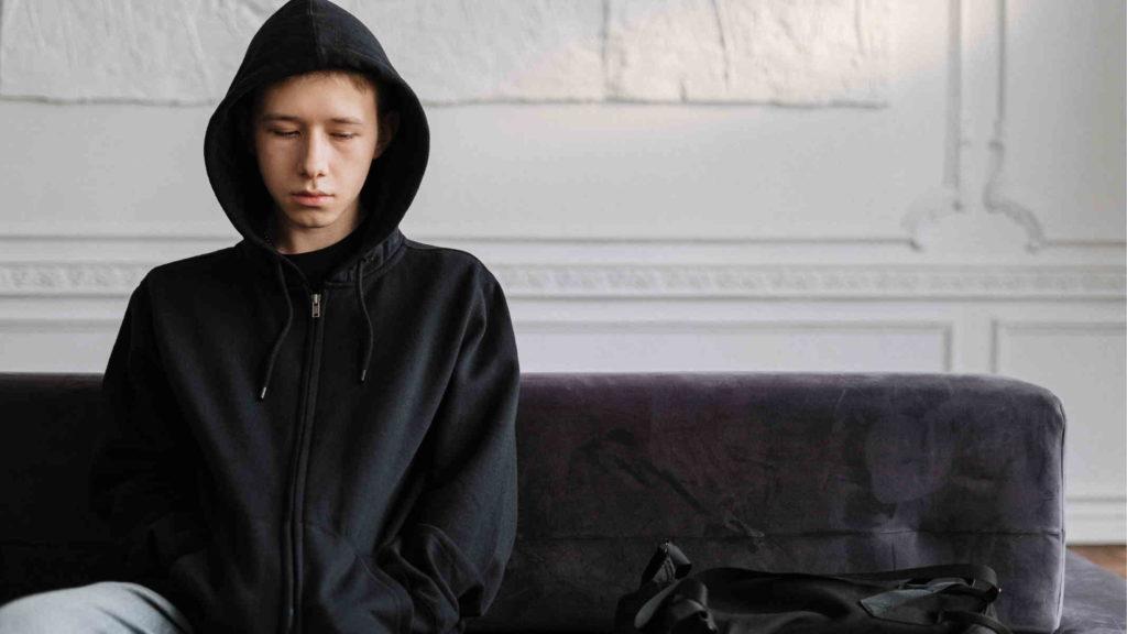 Подросток в черной толстовке сидит на диване