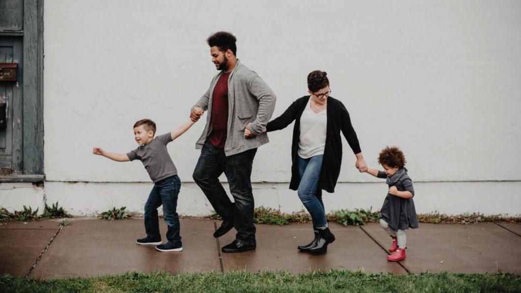 Семья идет по дороге и держится за руки
