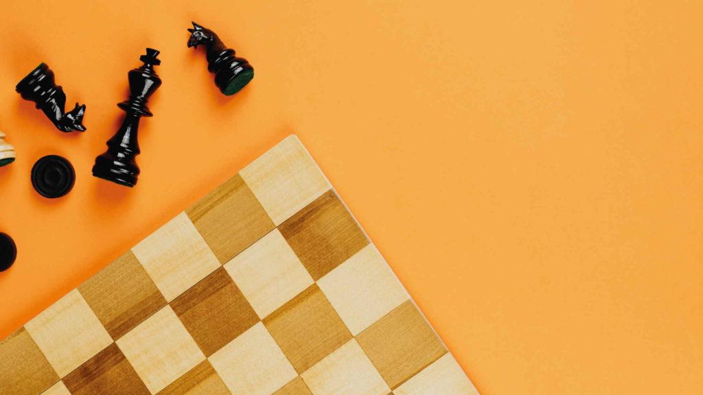 Шахматная доска и фигуры на оранжевом столе