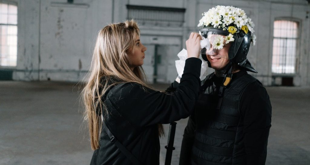 Девушка клеит цветы на шлем спецназа