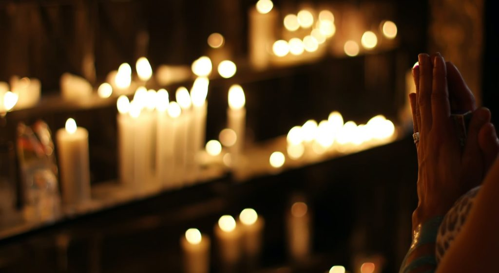 Девушка молится напротив заженных свечь