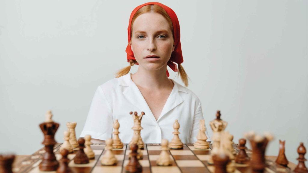 Комсомолка играет в шахматы в красном платке