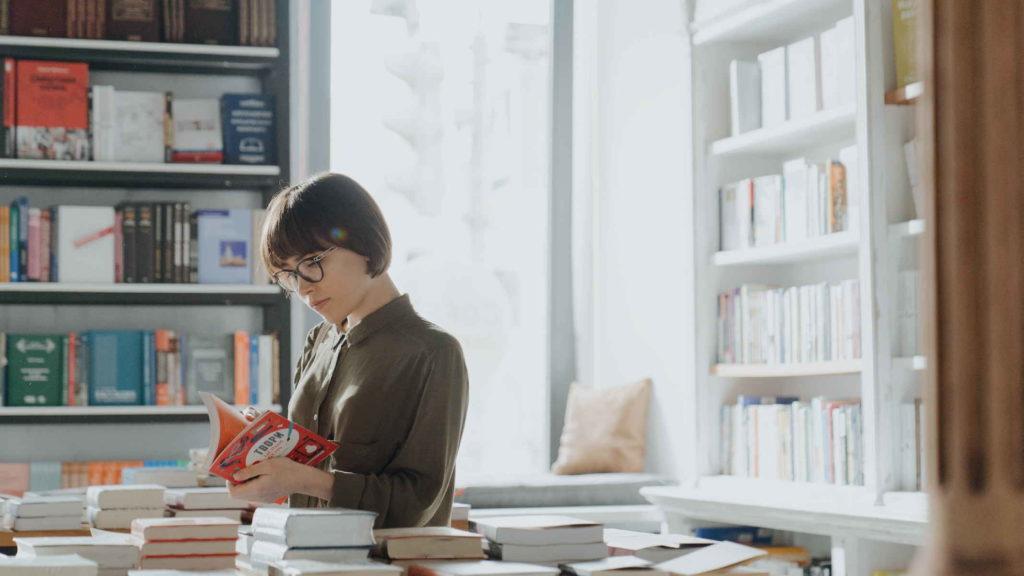 Молодая девушка выбирает себе книгу в магазине