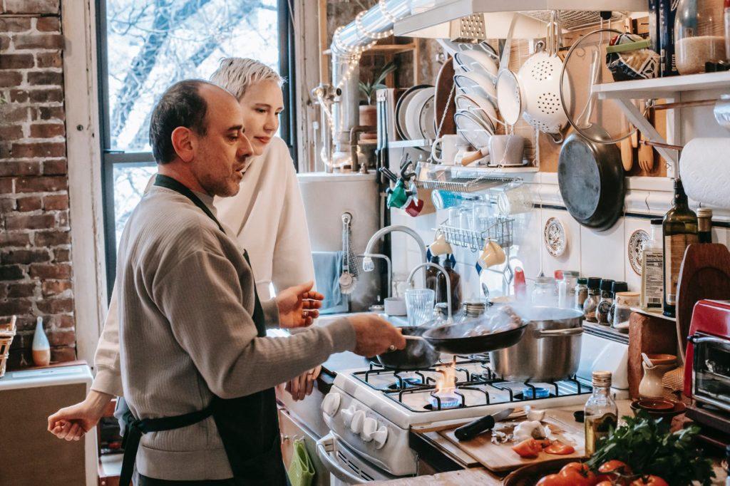 Мужчина готовит на сковороде