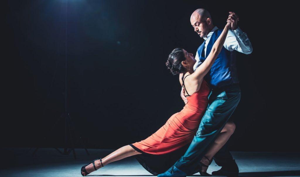 Мужчина и девушка танцуют на паркете