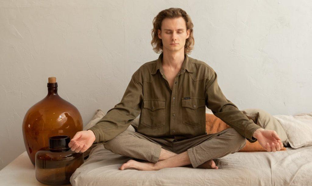 Мужчина медитирует на кровати