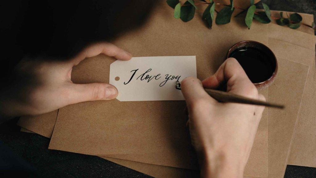 Мужчина пишет пером на пергаменте про любовь
