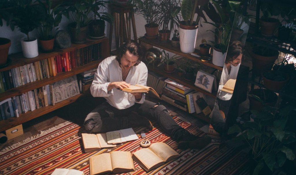 Мужчина сидит на полу вокруг книг