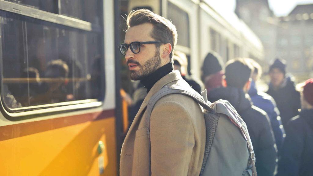 Мужчина стоит у автобуса и тревожно смотрит вдаль