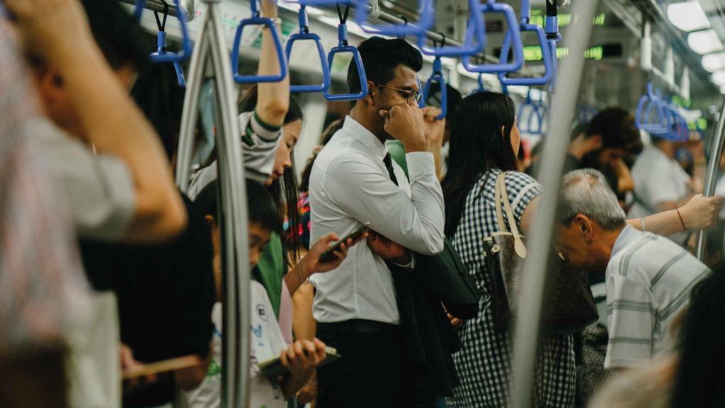 Мужчина стоит в поезде и держится за ручки