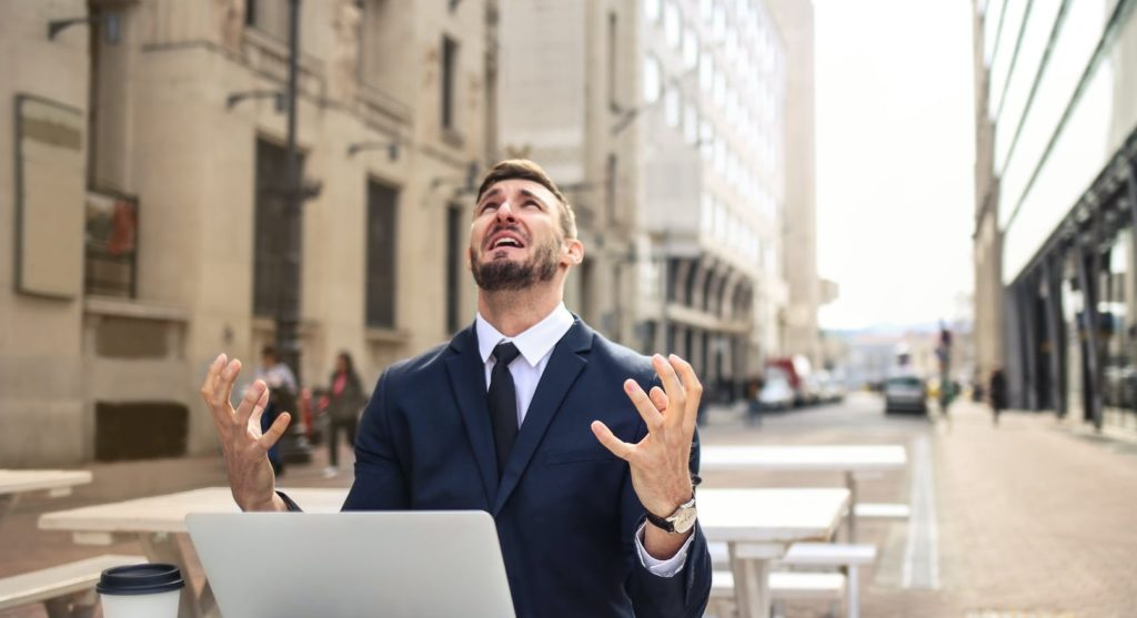 Мужчина страдает и сидит на улице с ноутбуком