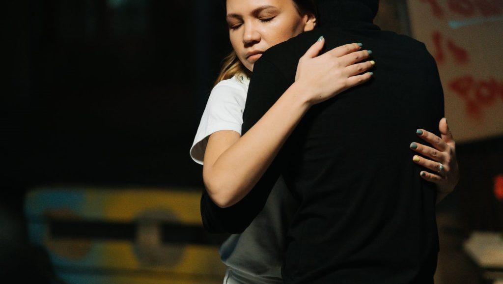 Пацифистка обнимает человека в черном