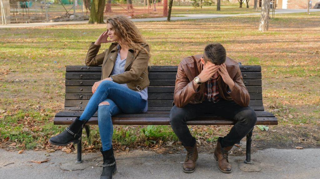 Парень и девушка сидят на лавке