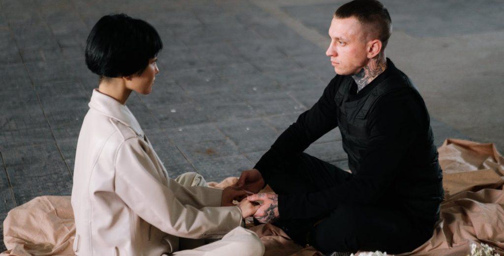 Парень и девушка сидят на покрывале на полу