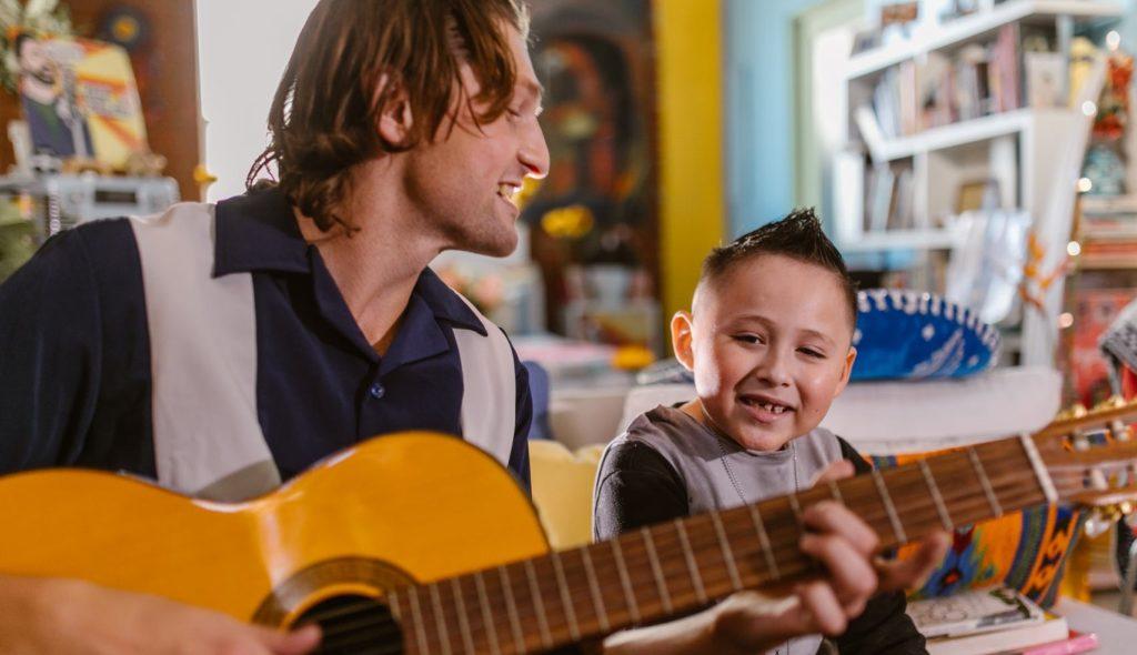Парень играет на гитаре перед мальчиком