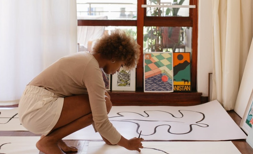 Женщина рисует на плакате на полу