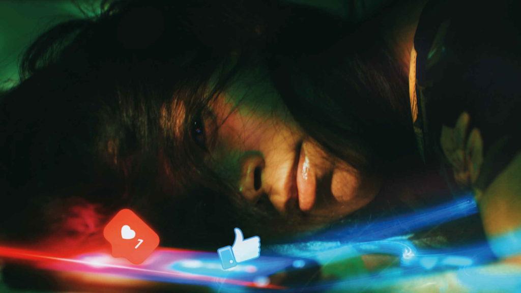 Безэмоциональная девушка лежит и смотрит на экран телефона