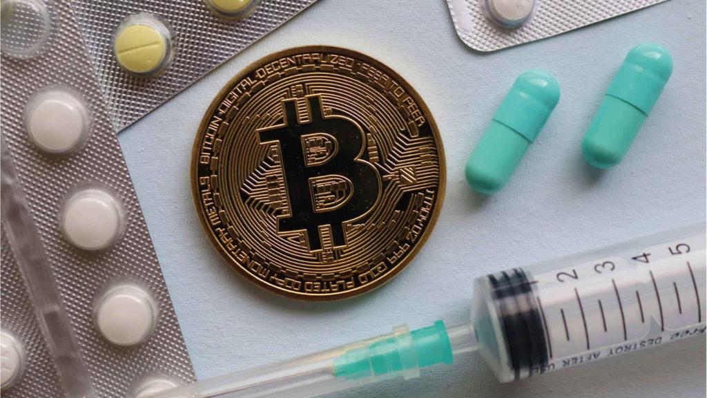 Биткоин таблетки и шприц лежат на белом столе