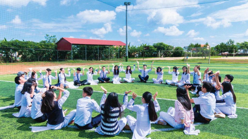 Большая группа людей сидит на зеленой лужайке