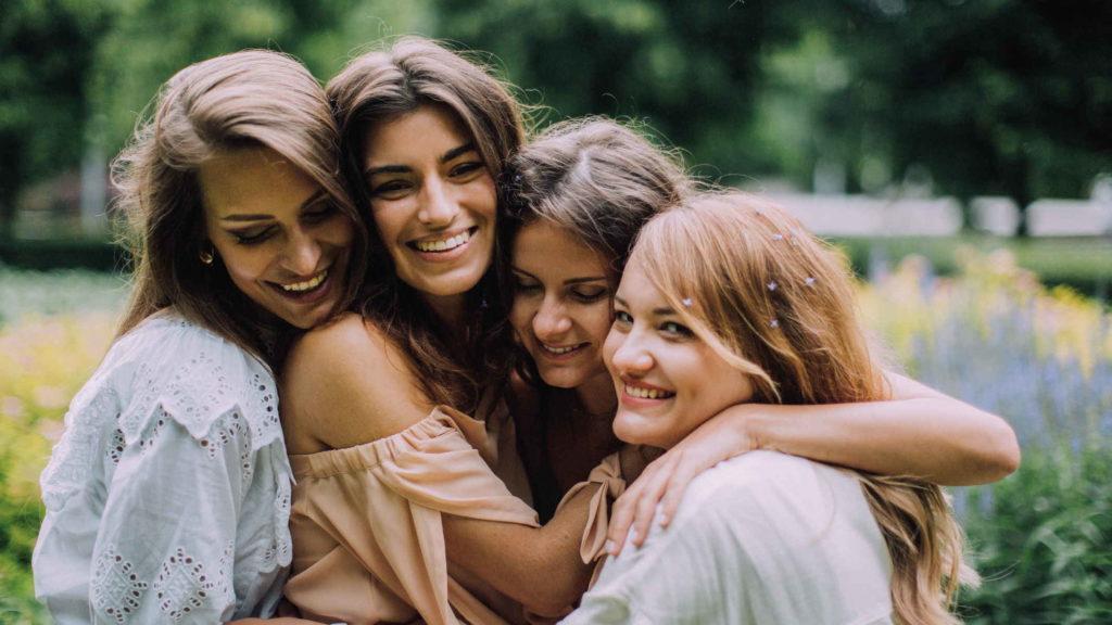 Четыре подруги на природе обнимаются