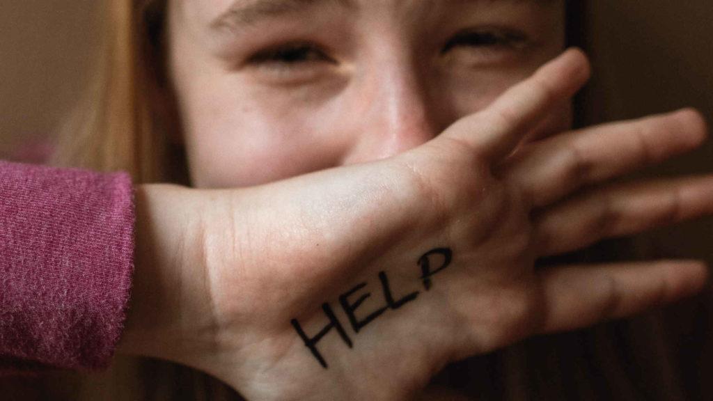Девочка закрывает лицо ладонью с надписью помогите