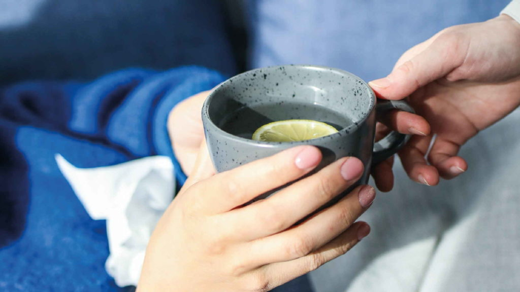 Девушка держит чашку чая с лимоном в руках