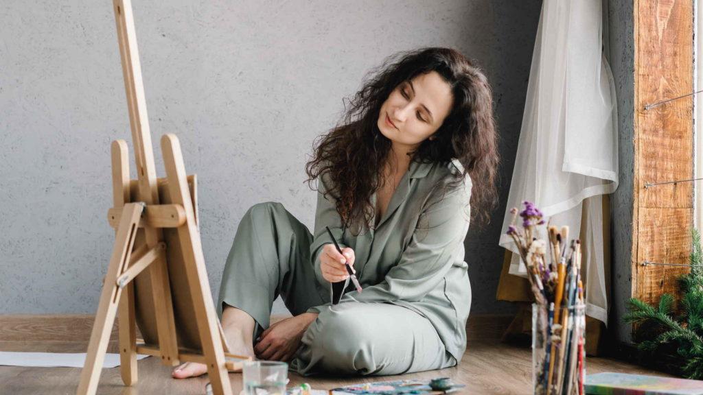 Девушка художник сидит на полу и пишет картину на мольберте маслом