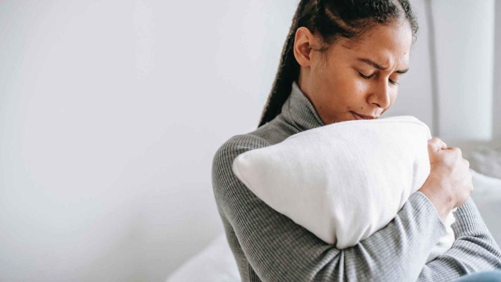 Девушка обнимает подушку и грустит