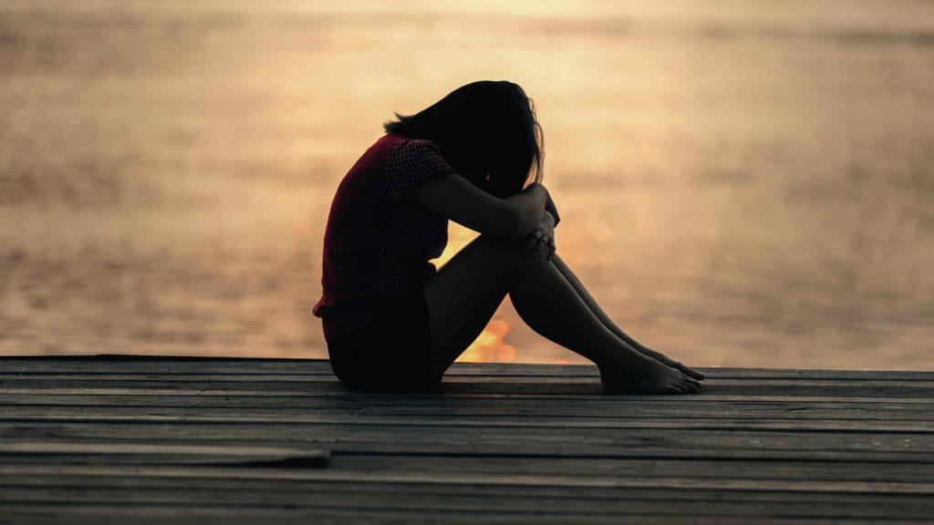 Девушка сидит на мосту на фоне заката
